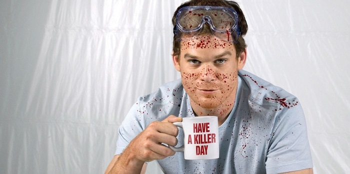 A blood spattered Dexter holding a coffee mug.